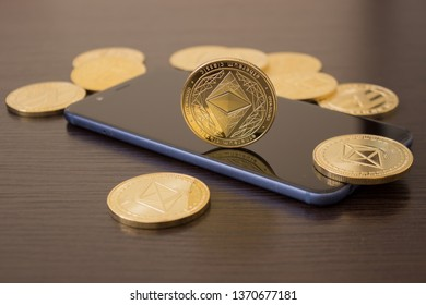 Golden Etherium coin close up on smartphone - business concept of crypto currency.