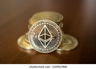 Golden Etherium coin close up. Ether is a cryptocurrency whose blockchain is generated by the Ethereum platform.