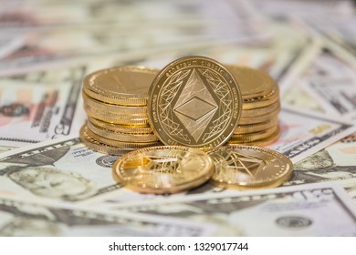 Golden Etherium coin on us dollars close up.