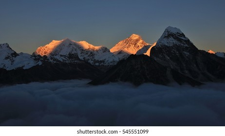 Golden evening light illuminate Mt Everest. Mt Everest and other hight mountains of the Himalayas at sunset. Sea of fog.