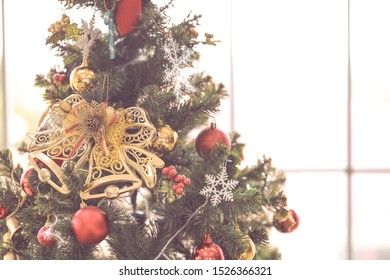 Golden fake toy bell and ornaments decorated hanging on Christmas tree with copy space placed near window , processed in retro vintage style.