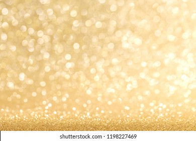 Golden festive glitter background with defocused lights