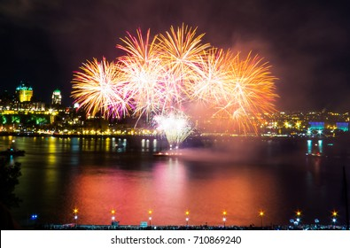Golden fireworks over the Saint-Lawrence River with a part of Quebec city in the background. Quebec, Canada.