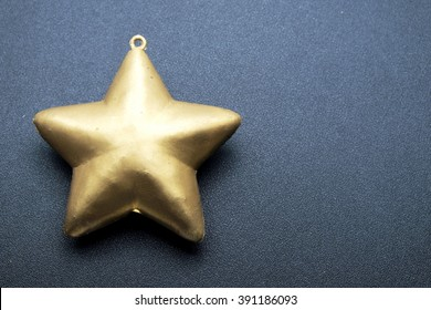 Golden five pointed star decoration on black background. Space for texts.