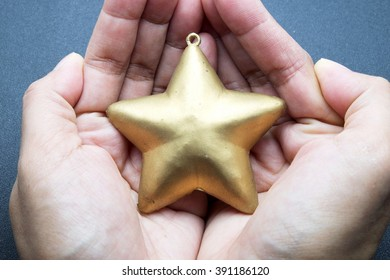 Golden five pointed star decoration in hands on black background.