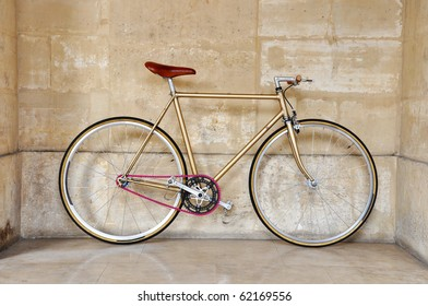 A golden fixed-gear bicycle (also called fixie) with a pink chain