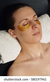 Golden flakes with collagen. Cosmetic procedure, the woman's face with gold flakes under the eyes