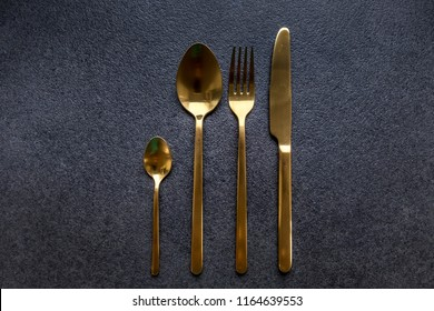 golden flatware on dark grey background