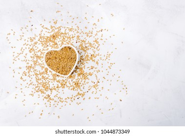 Golden flax seeds in a heart shaped bowl with scattered seeds around on white wooden surface