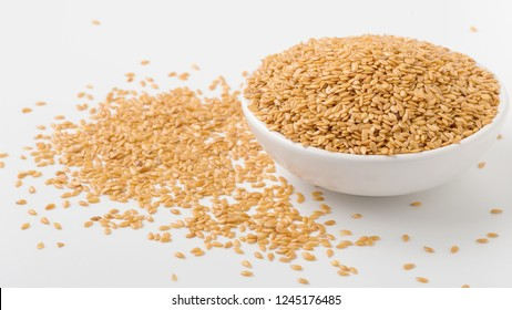 Golden flaxseed in bowl with flaxseed on white background