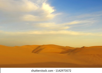 golden fluorescent cirrus clouds over orange sand dunes of the endless Taklamakan desert at sunset, China