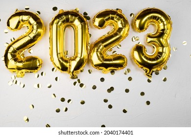 golden foil balloon 2023 New Year. Numbers two thousand twenty three from a foil figure on a gray cement background. Golden confetti and celebration. Copy space