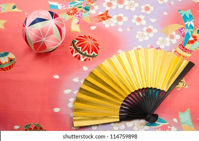 Golden folding fan and traditional japanese handball on the designed old japanese cloth