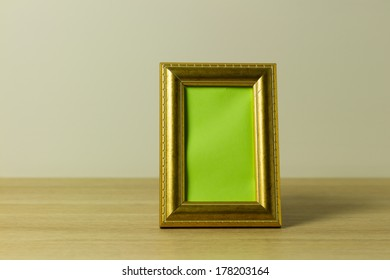 golden frame with green place holder standing on wooden surface