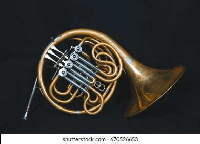 Golden french horn with black background