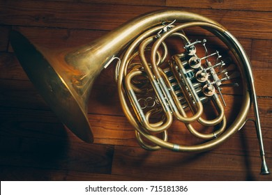 Golden french horn with Wooden Background