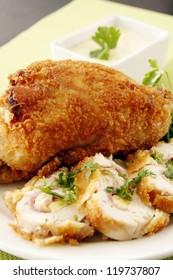 A golden fried chicken stuffed with vegetable garnishing