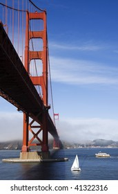 Golden Gate Bridge from below, featuring yachts and the typical fog rolling in.