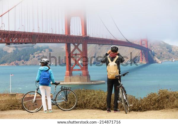 Golden gate bridge - biking couple sightseeing in San Francisco, USA. Young couple tourists on bike tour enjoying the view at the famous travel landmark in California, USA.