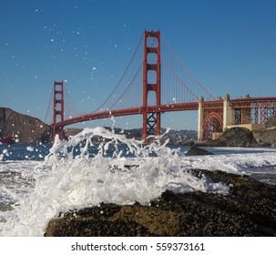 Golden Gate Bridge in California and spray of the sea on the shore
