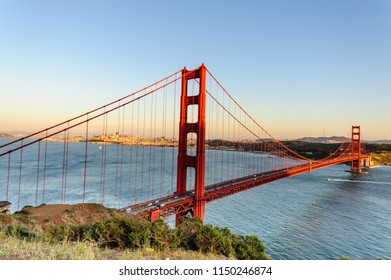 The Golden Gate Bridge, with Down Town San Francisco, and de San Francisco Bay Area as a background, during the sunset golden hour. Image taken from from Battery Vista in Marin County, California.