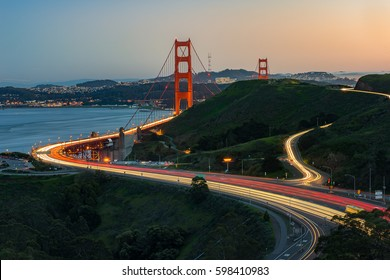 Golden Gate Bridge and light trail of Highway 1 during sunset