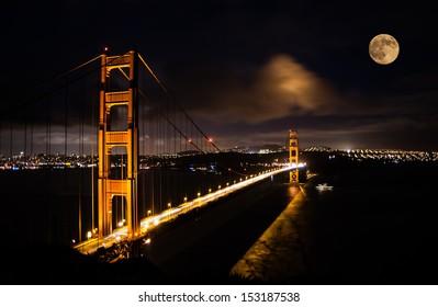 Golden Gate bridge at night with full moon shining on San Francisco skyline