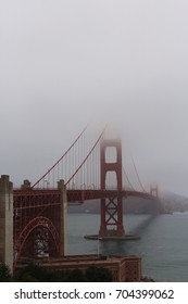 The Golden Gate Bridge on a very foggy day with half of the towers enveloped in fog, taken from the Golden Gate Bridge Welcome Center, San Francisco, California, USA
