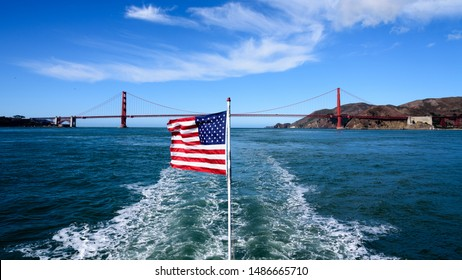 Golden Gate Bridge in San Francisco with a USA flag.