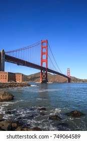 Golden Gate bridge from the San Francisco side. View of Fort Mason on the left and rocks in the foreground. A blue sky is in the background. It is a vertical image.