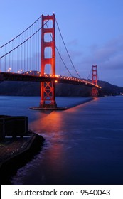Golden Gate Bridge as seen from Fort Point overlook is glowing in the dusk after a winter storm