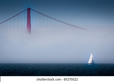 Golden Gate Bridge Shrouded in Fog with Sailboat in San Francisco Bay