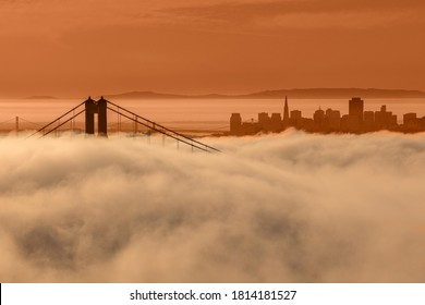 The Golden Gate bridge and skyscrapers are shown in a fog against a red sky due to fires, San Francisco, California