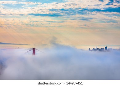 Golden Gate Bridge in thick fog and outline of San Francisco after Sunrise
