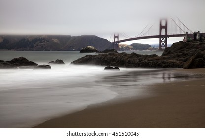 Golden Gate Bridge through the fog behind a scenic beach
