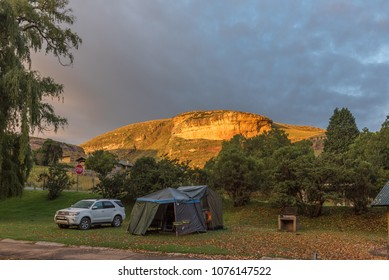GOLDEN GATE HIGHLANDS NATIONAL PARK, SOUTH AFRICA - MARCH 14, 2018: A golden sandstone cliff at sunrise with a tent and vehicle in the Glen Reenen Rest Camp in front