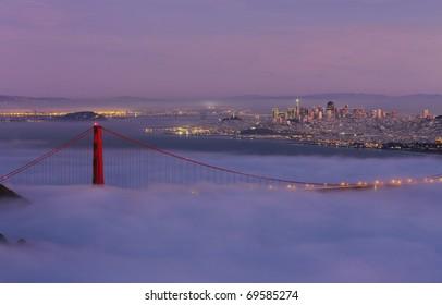 GOLDEN GATE NATIONAL RECREATION AREA, CALIFORNIA: Golden Gate Bridge taken from Hawk Hill overlook in Marin County with fog flowing over bridge at twilight.