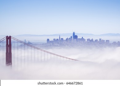 Golden Gate and the San Francisco bay covered by fog, the financial district skyline in the background, as seen from the Marin Headlands State Park, California