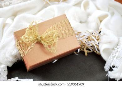 Golden gift box put on white scarf background