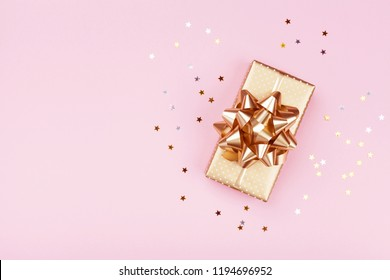 Golden gift or present box and stars confetti on pink table top view. Flat lay composition for birthday, christmas or wedding.