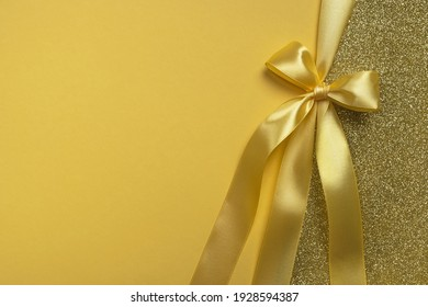 Golden gift shiny card, certificate or texture gift box with yellow ribbon bow. Christmas, new year, birthday, anniversary or sale background. Top view, flat lay, copy space, template for design