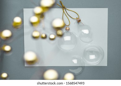 Golden and glass Christmas decorations on the white and grey background. blurred golden balls in the foreground and transparent glass balls for New Year's decor