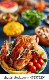 Golden glistening roasted turkey decorated with vegetables and rosemary, on thanksgiving dinner table filled with dishes and food, pumpkin in background