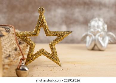 Golden glitter Christmas star over wooden background
