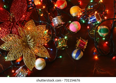 golden glitter flower christmas lights and christmas tree decoration on red background with copy space