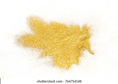Golden glitter sand texture, handful spread on white, abstract background with copy space, top view. Yellow dusty shimmer decoration pile, shiny and sparkling. Holiday and glamour concept.