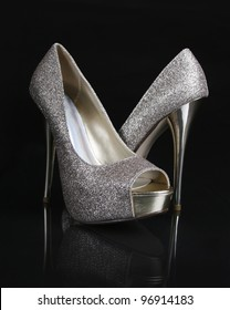 golden glitter shoes on black background