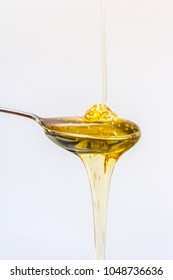 golden glossy liquid honey dripping onto metal spoon with white background