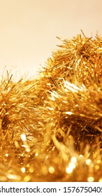 Golden glutter garland with a blurry foreground against a white background.