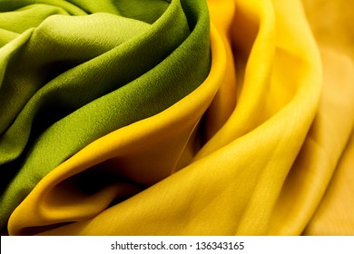Golden and green satin textile background (close up)